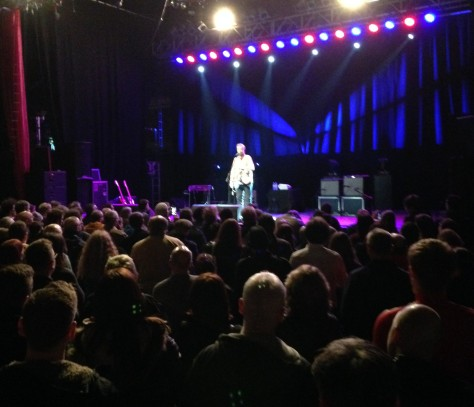Billy Bragg cuts a strong figure alone on stage belting out to a captivated public.